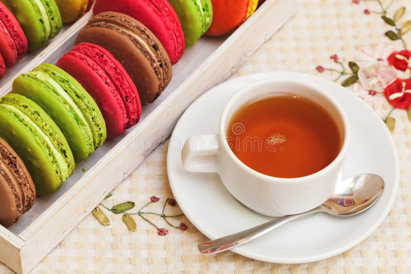 Macarons variopinti francesi tradizionali in una scatola, tazza di tè immagine stock libera da diritti