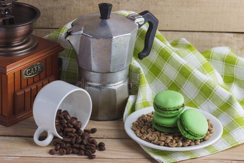 Macarons verdes en la placa, la taza, el pote del café y la servilleta de la tela escocesa imagen de archivo