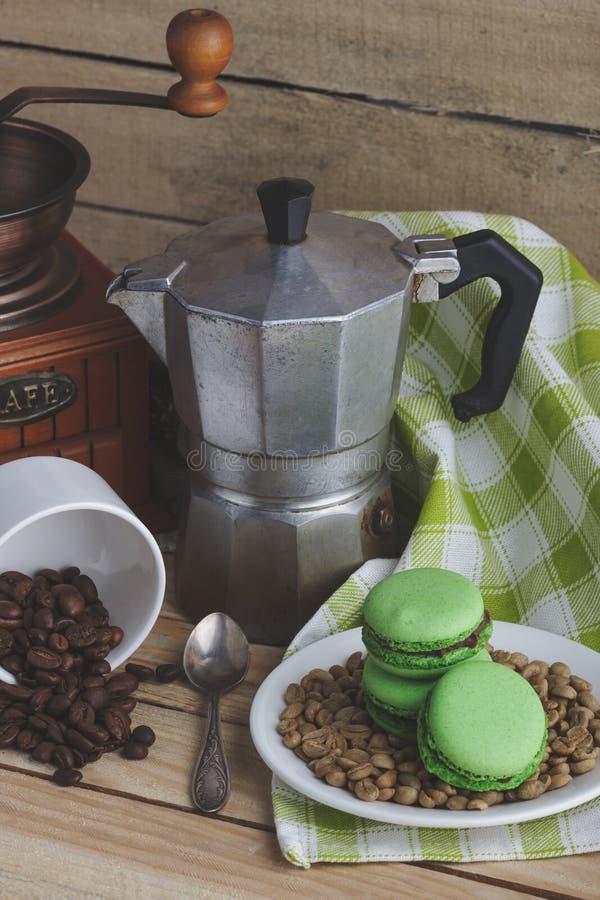 Macarons verdes en la placa, la taza, el pote del café y la servilleta de la tela escocesa foto de archivo libre de regalías