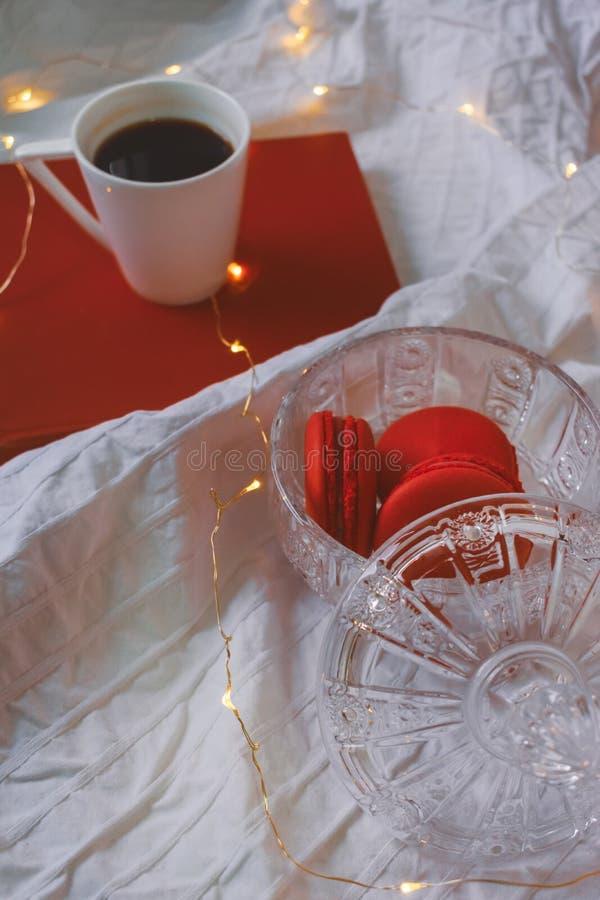 Macarons vermelhos na bacia de cristal, no livro e em um café imagem de stock