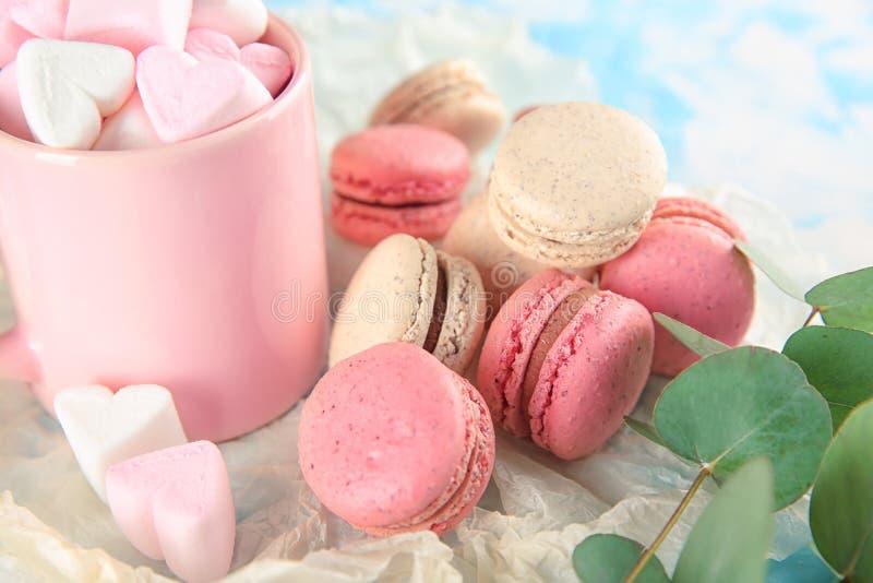 Macarons y taza sabrosos con las melcochas en la tabla fotos de archivo