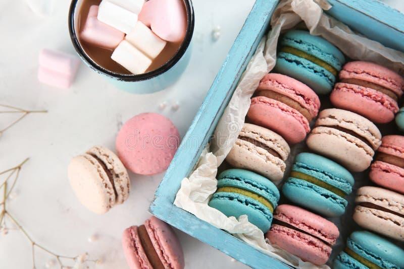 Macarons y taza sabrosos de café con las melcochas en fondo ligero imagenes de archivo