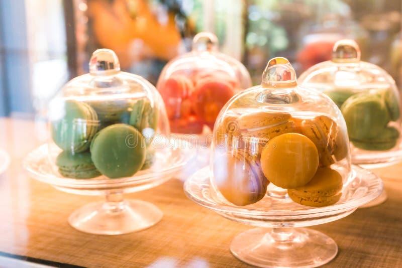 Macaronsna i tre exponeringsglasklockakrus och dem är i coffee shop royaltyfria foton