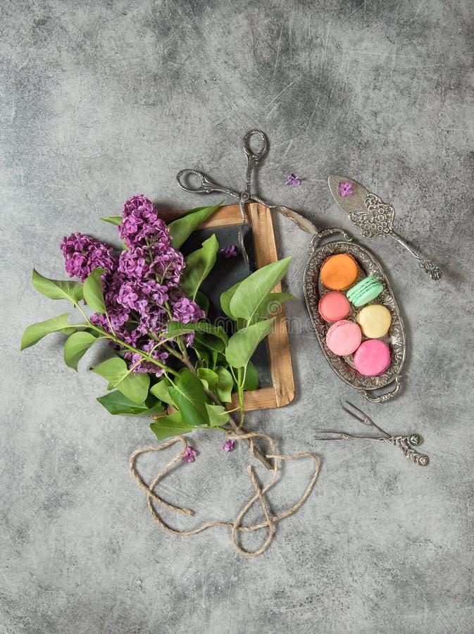 Macaroon εκλεκτής ποιότητας ακόμα ζωή διακοσμήσεων λουλουδιών μπισκότων ιώδης στοκ φωτογραφία με δικαίωμα ελεύθερης χρήσης