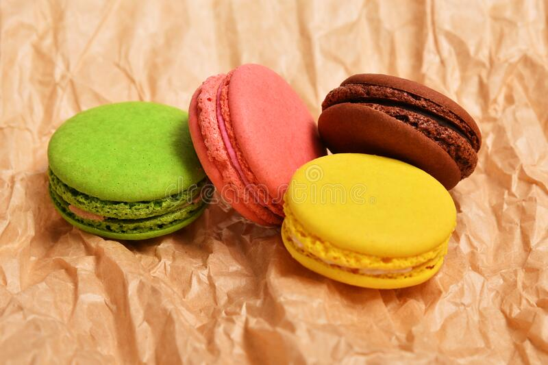 Macaroon colorful french cake delicious. On the paper background stock images