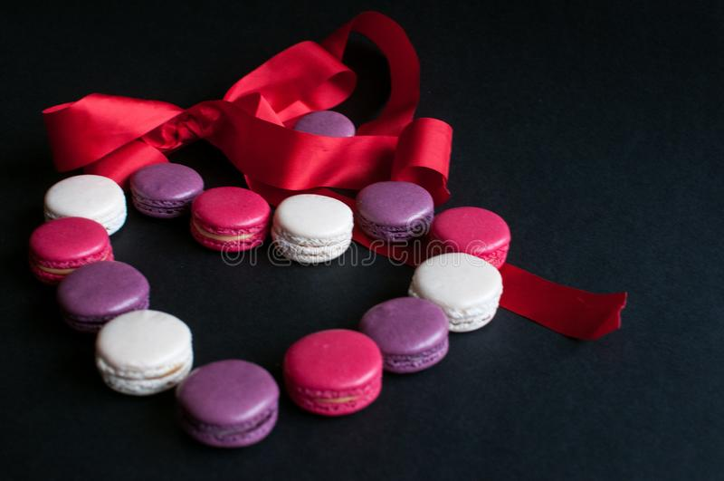 Macaroon laid out on a black background in the form of a heart with red ribbon. colorful almond cookies, pastel colors. Present stock photos