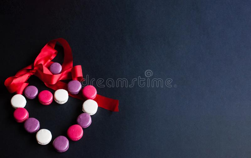 Macaroon laid out on a black background in the form of a heart with red ribbon. colorful almond cookies, pastel colors. Present royalty free stock image