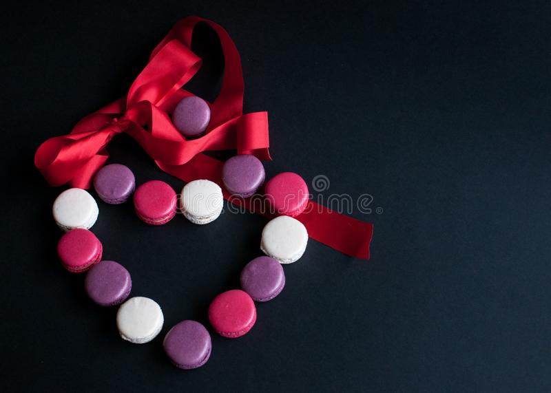 Macaroon laid out on a black background in the form of a heart with red ribbon. colorful almond cookies, pastel colors. Present royalty free stock photography
