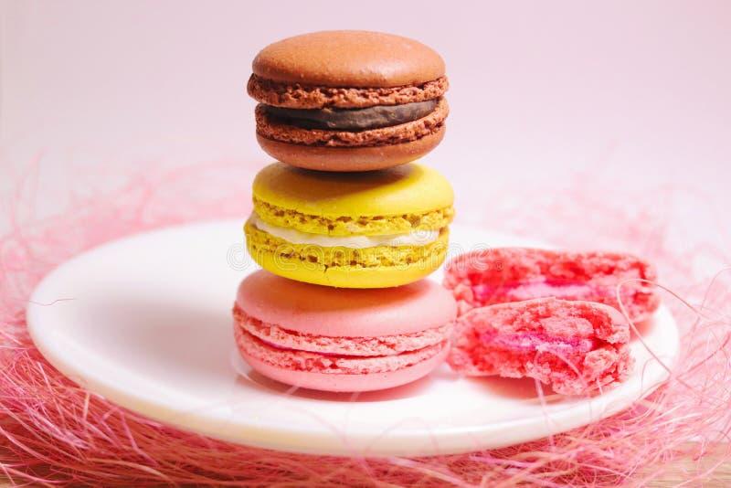 Macaroons σωρός των διαφορετικών χρωμάτων που στέκονται στο άσπρο πιάτο Μπροστινή όψη στοκ εικόνα