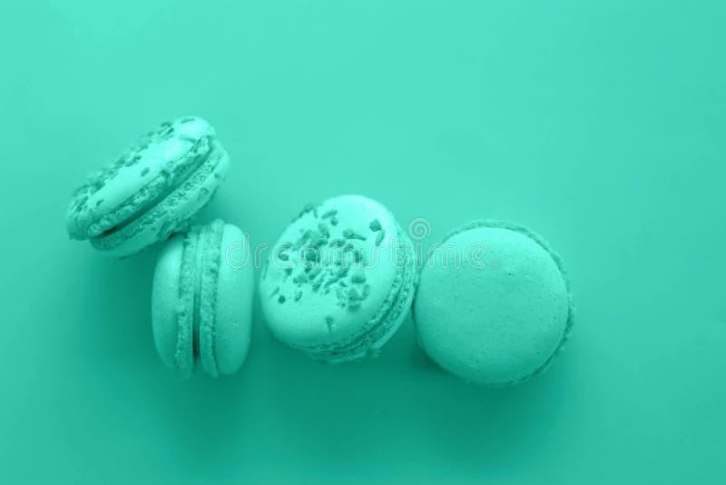 Macaroons του πλούσιου μπλε με τα τυρκουάζ χρώματα σε ένα μπλε υπόβαθρο στοκ εικόνα