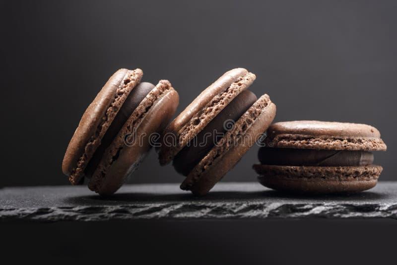 3 macaroons закрывают вверх на каменном блюде на черноте стоковое фото