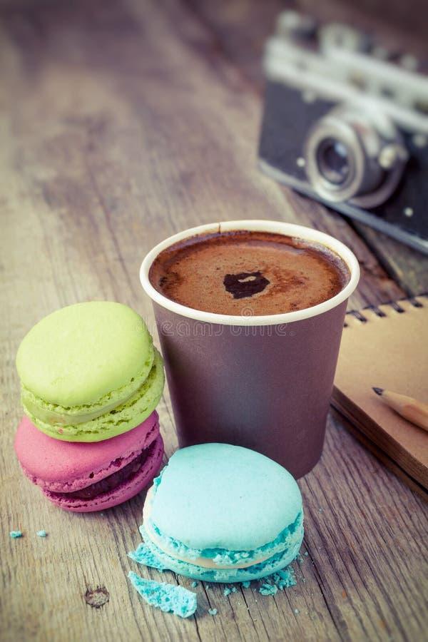 Macaroons, кофейная чашка эспрессо, книга эскиза и ретро камера дальше стоковое фото rf