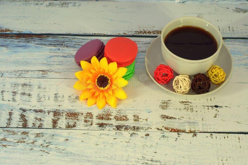 Macaroons, кофе, Баалы и цветок на таблице стоковое изображение