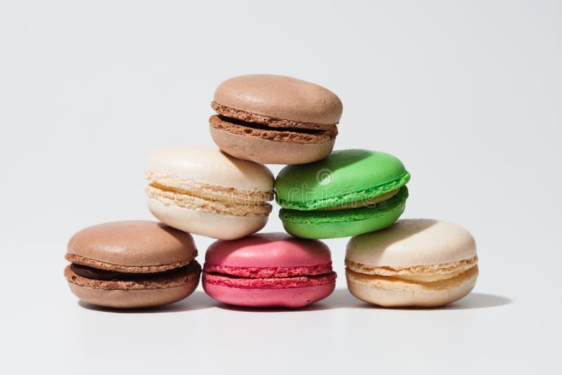 Macaroons на белой предпосылке Красочная французская сладостная сортированная пирамида деликатеса Бежевые розовые зеленые коричне стоковые изображения rf