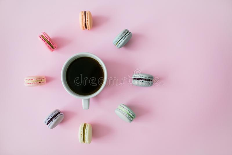 Macaroons around coffee cup on a pink background. Flatlay royalty free stock photos