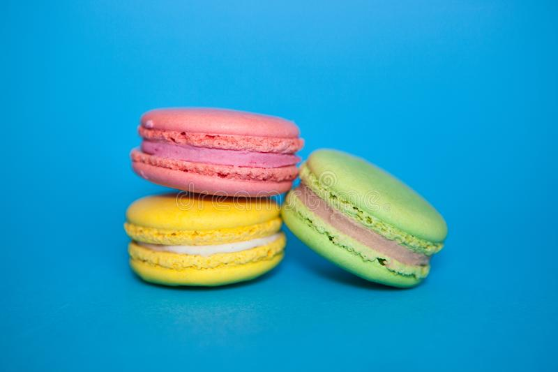 Macaroons biscuits on blue background, yellow, pink and green colors. French Macaroons biscuits on blue background, yellow, pink and green colors, sweet food stock photos