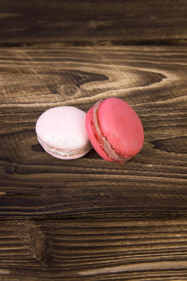 macaroons on a brown table. two makura on the table. pink macaroons. packaging option stock photos