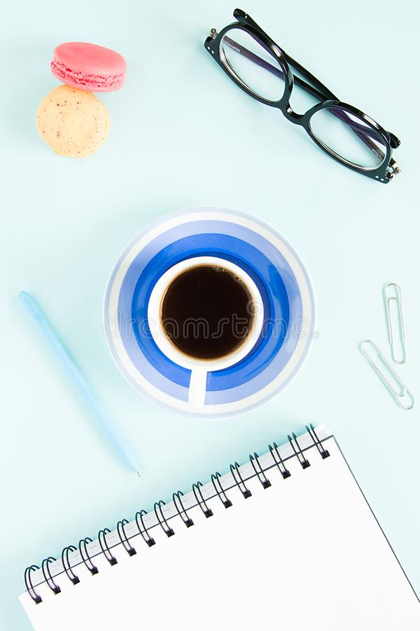 Macaroons, a cup of black coffee, an open note with white page, pen, glasses on a pastel blue background. Image for your design. / stock image