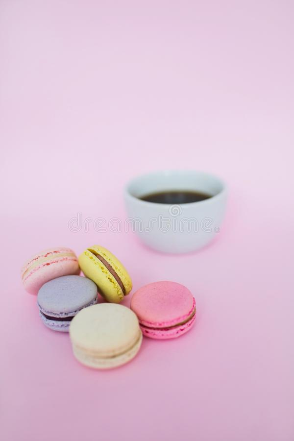 Macaroons and a cup of coffee on a pink background. stock photos