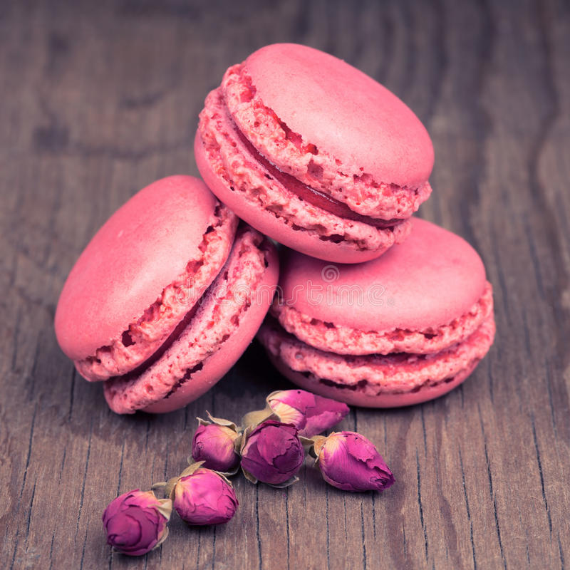 Macaroons with dry roses on vintage wooden background royalty free stock photography