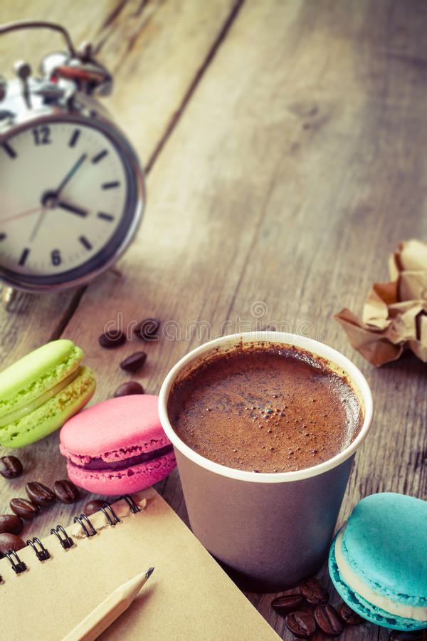Macaroons, espresso coffee cup, sketch book and alarm clock royalty free stock images
