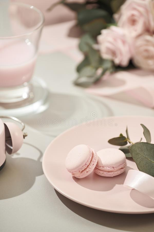 Macaroons in pastel colors with bouquet of pink roses flowers on white background. Beautiful holiday background. copy space royalty free stock photo