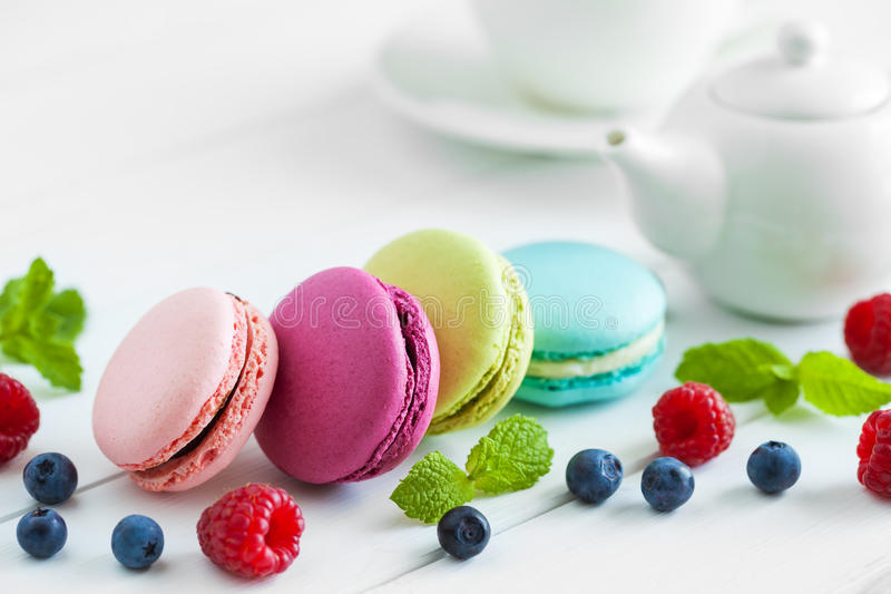 Macaroons, raspberries, blackberries and teapot with cup of tea royalty free stock image