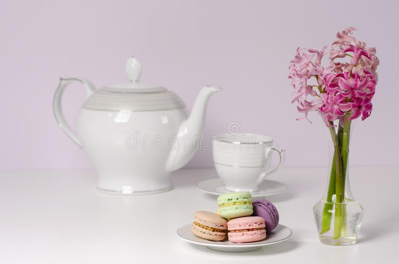 Macaroons and transparent vase with pink hyacinth flowers on porcelain tea pot and cup background. Selective focus. Breakfast dessert concept. Copy space stock images