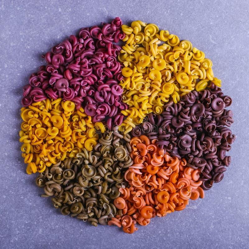 Macarrão colorido da forma incomum com as tinturas vegetais naturais, alinhado em um círculo close up do fundo foto de stock royalty free