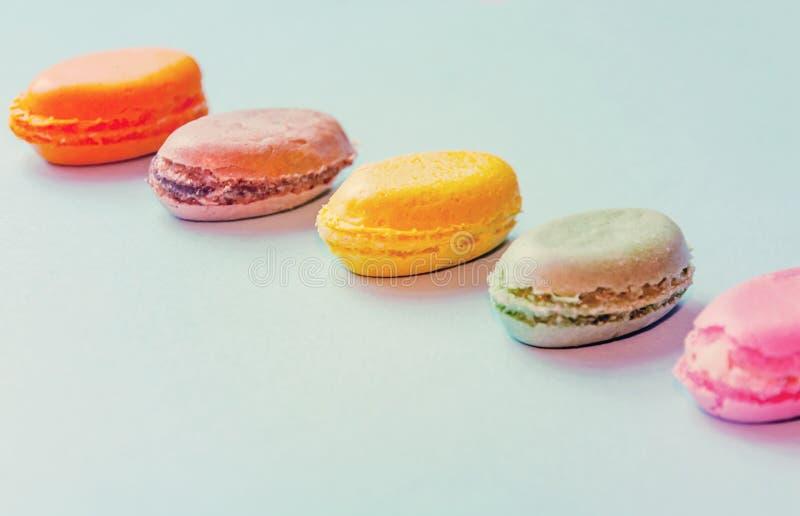 Macarrão colorido da sobremesa francesa no fundo azul fotografia de stock