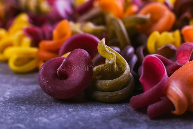 macarrão Multi-colorido de um formulário incomum com as tinturas vegetais naturais Fim macro do fundo acima foto de stock royalty free