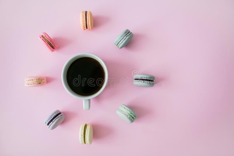 Macarrones alrededor de la taza de café en un fondo rosado flatlay fotos de archivo libres de regalías