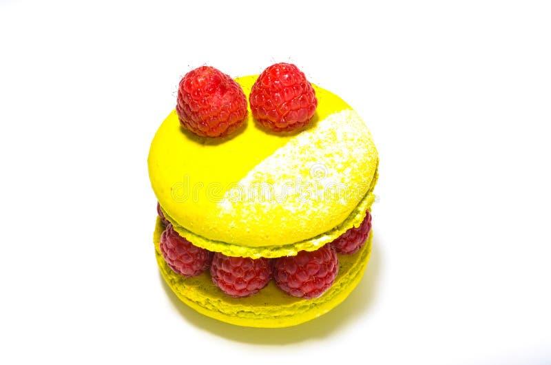 Macarrones amarillos del limón con las frambuesas frescas foto de archivo libre de regalías
