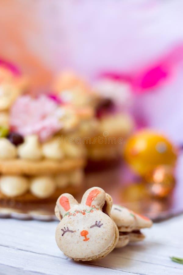 Macarrones anaranjados con los macarrones del relleno del chocolate y del conejito de pascua, en el fondo anaranjado de Tulle foto de archivo libre de regalías