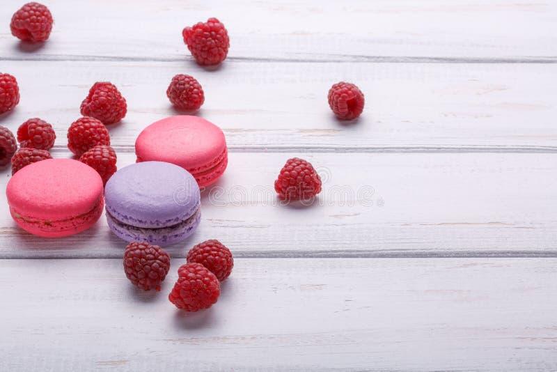 Macarrones coloridos deliciosos de las galletas con las frambuesas sobre el fondo de madera blanco Espacio para el texto foto de archivo libre de regalías