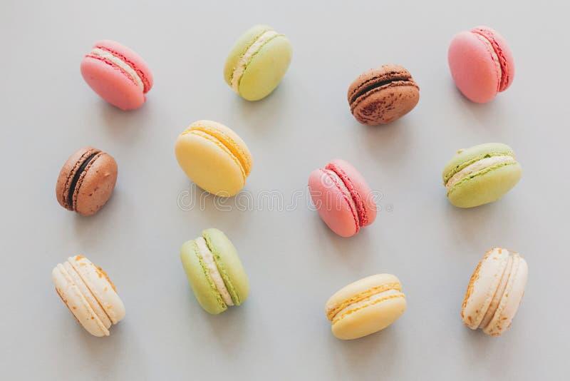 Macarrones coloridos deliciosos en el la plano de papel gris en colores pastel de moda foto de archivo libre de regalías