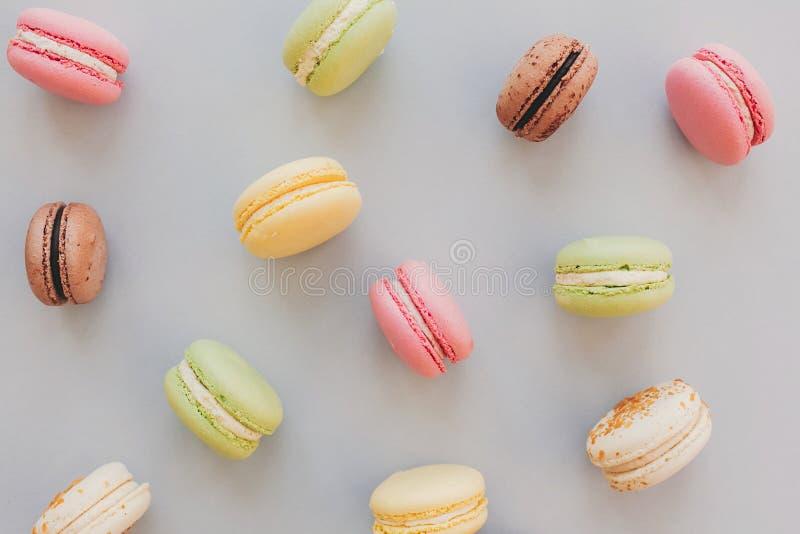 Macarrones coloridos deliciosos en el la plano de papel gris en colores pastel de moda imagen de archivo libre de regalías