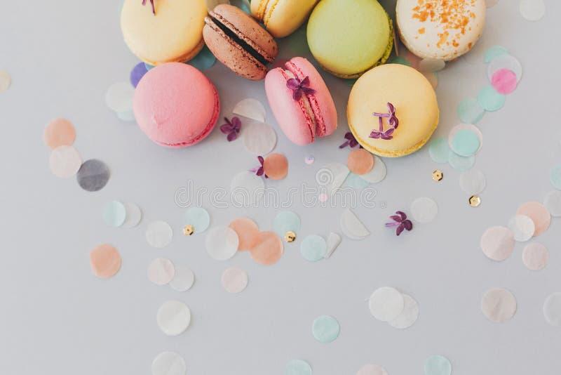 Macarrones coloridos deliciosos en el papel gris en colores pastel de moda con li imagen de archivo