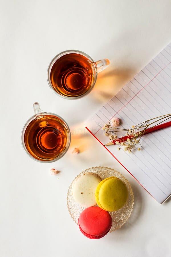 Macarrones franceses coloridos con dos tazas de té en la endecha blanca del plano foto de archivo