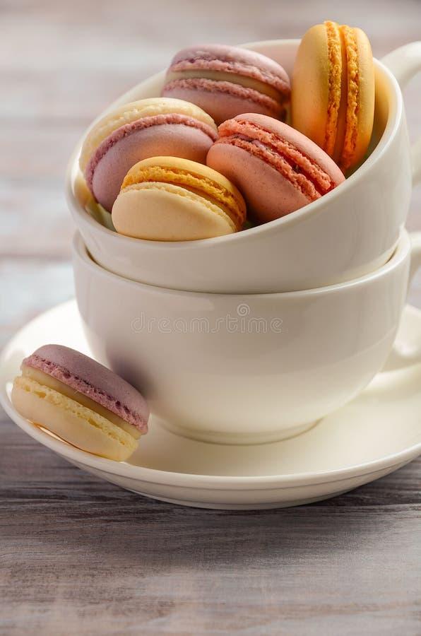 Macarrones franceses coloridos en la taza blanca en fondo de madera foto de archivo libre de regalías