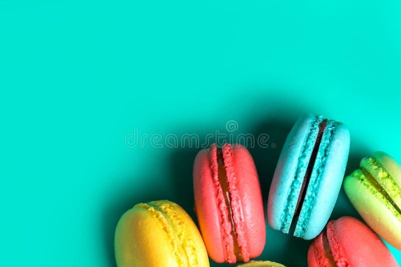 Macarrones franceses dulces y coloridos en fondo de la turquesa con el espacio de la copia, visión superior, cierre para arriba imagenes de archivo