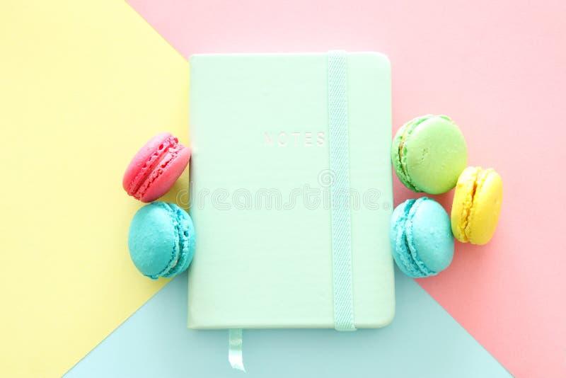 Macarrones multicolores en el cuaderno geométrico en colores pastel del fondo y del vintage fotografía de archivo libre de regalías