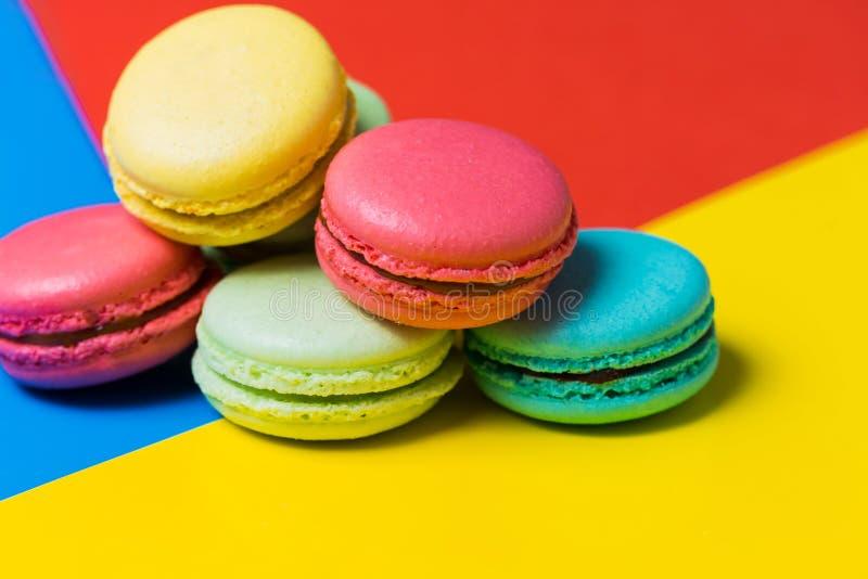 Macarrones o macaron franceses dulces y coloridos en fondo colorido fotos de archivo libres de regalías