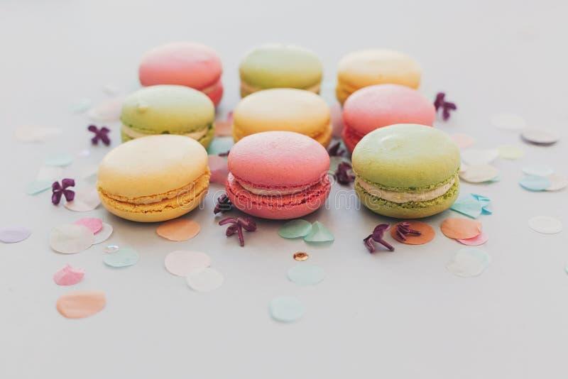 Macarrones rosados, amarillos, verdes sabrosos en el papel gris en colores pastel de moda imagenes de archivo