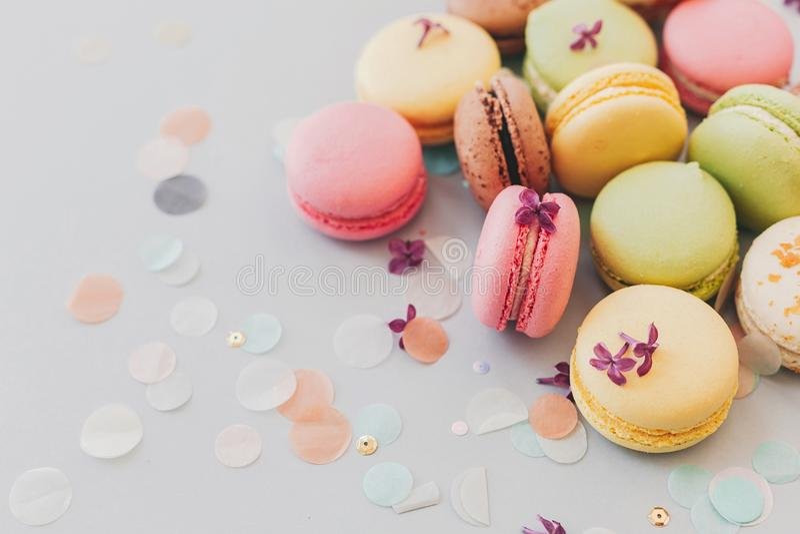 Macarrones rosados, amarillos, verdes y marrones sabrosos en el pastel de moda g foto de archivo
