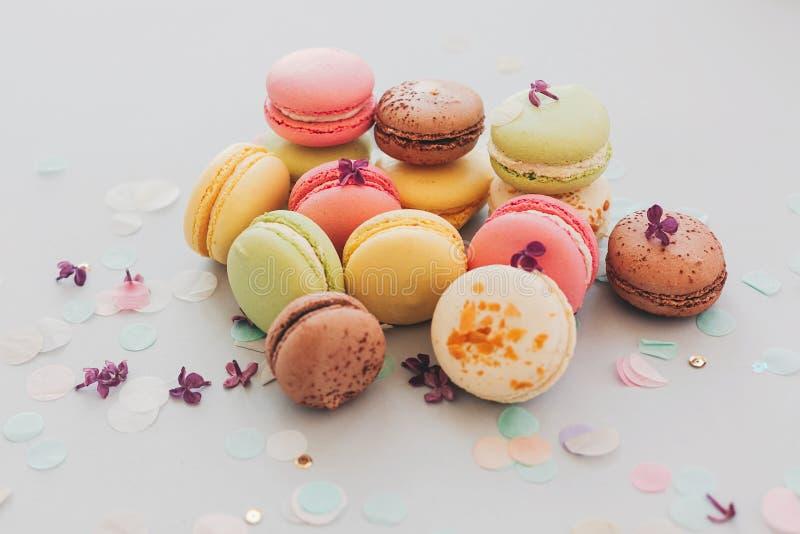 Macarrones rosados, amarillos, verdes y marrones sabrosos en el pastel de moda g imagen de archivo libre de regalías