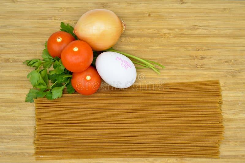 Macarrones, tomates, huevo y cebolla crudos y frescos imagen de archivo