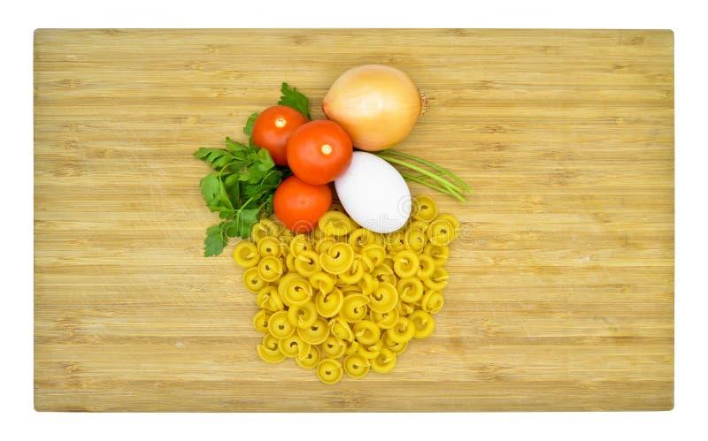 Macarrones, tomates, huevo y cebolla crudos y frescos foto de archivo libre de regalías