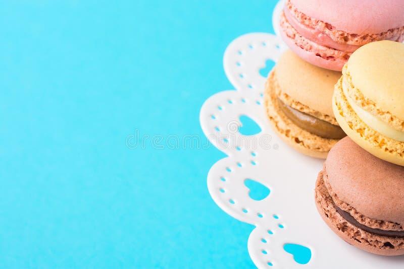 Macarrones verdes rosados multicolores del café de la moca de Brown amarillo apilados en el soporte blanco de la torta del cordón fotografía de archivo