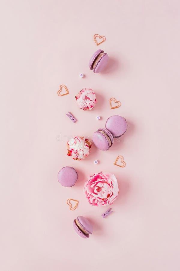 Macarrones y flores en un fondo rosado imagen de archivo libre de regalías